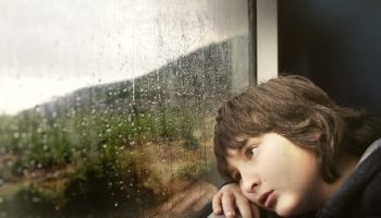 kid waiting by rainy window